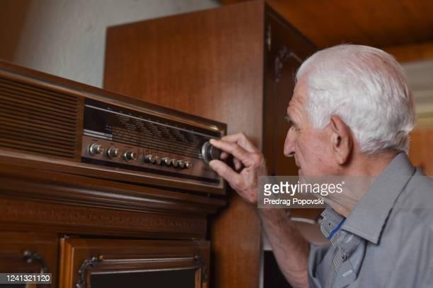portrait of senior man turning old lamp radio - radio stock pictures, royalty-free photos & images
