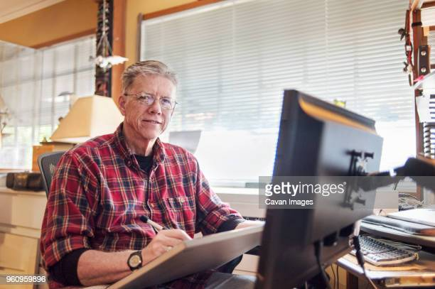 Portrait of senior man using graphics tablet at home
