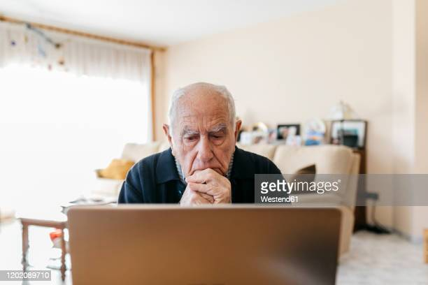 portrait of senior man using laptop at home - disappointment stock pictures, royalty-free photos & images