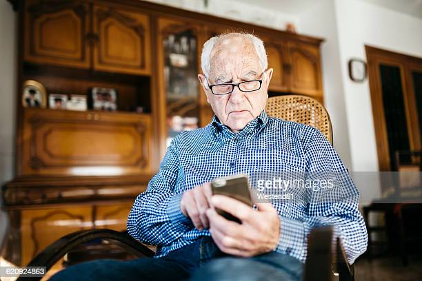 Portrait of senior man using smartphone at home