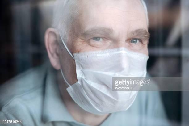portrait of senior man wearing a mask at home, looking out of the window - munskydd ensam bildbanksfoton och bilder