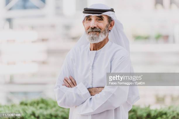portrait of senior man wearing dish dash with arms crossed - arab old man stock pictures, royalty-free photos & images