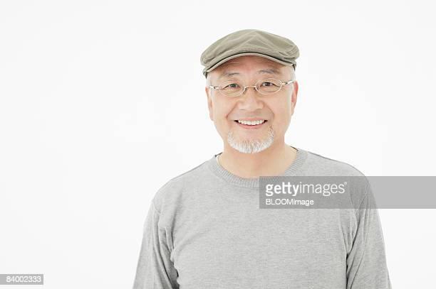Portrait of senior man wearing hat and glasses, studio shot