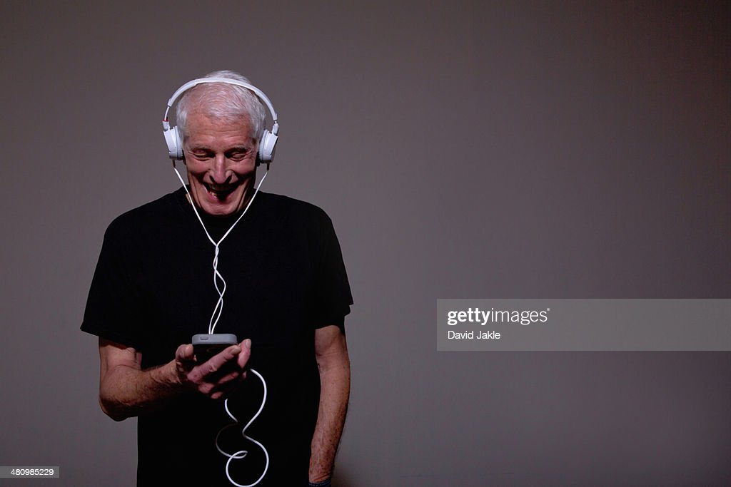 Portrait of senior man wearing headphones and using MP3 player : Stock Photo