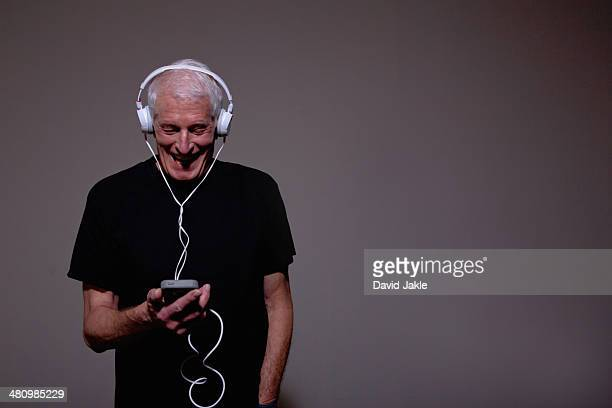 Portrait of senior man wearing headphones and using MP3 player