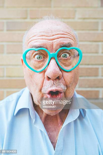 Portrait of senior man wearing heart-shaped glasses pulling funny faces