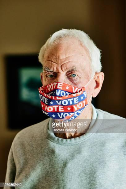 portrait of senior man wearing protective face mask that says vote - amerikaanse presidentsverkiezingen stockfoto's en -beelden