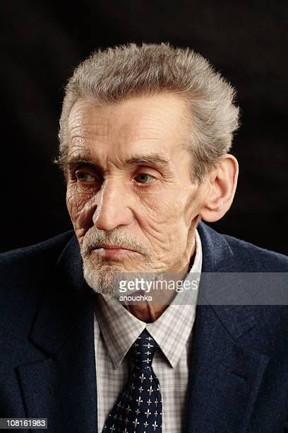 Porträt eines älteren Mannes tragen Anzug, isoliert auf Schwarz