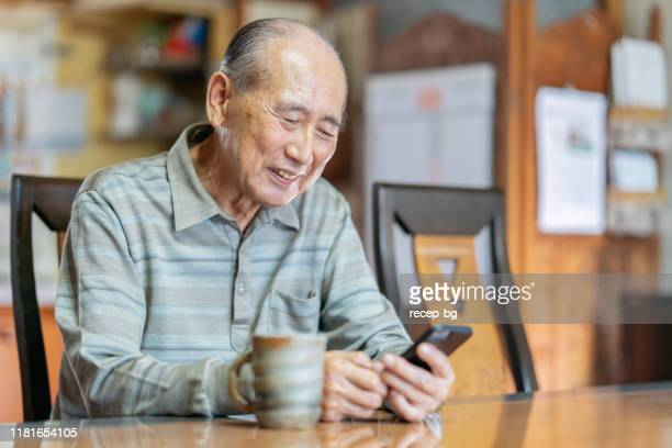 portrait of senior man while using smart phone - japanese old man stock pictures, royalty-free photos & images