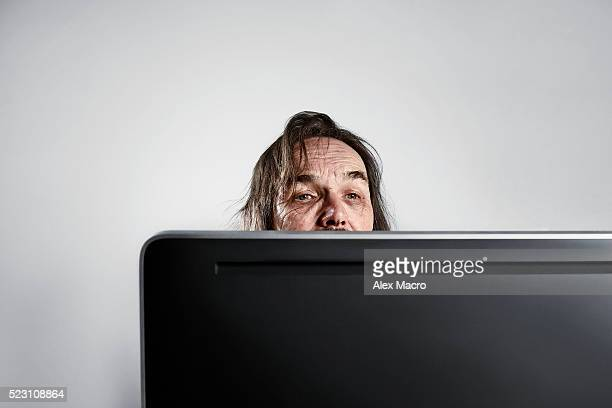 Portrait of senior man with computer monitor