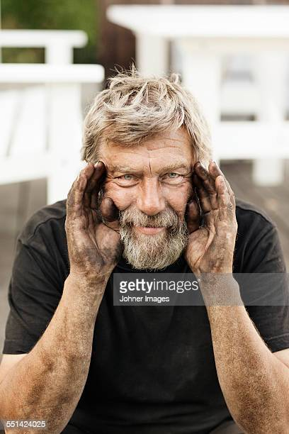 Portrait of senior man with dirty hands
