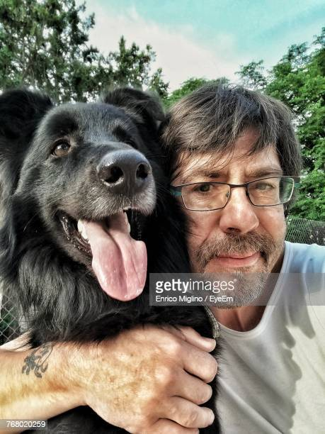 Portrait Of Senior Man With Dog Against Sky