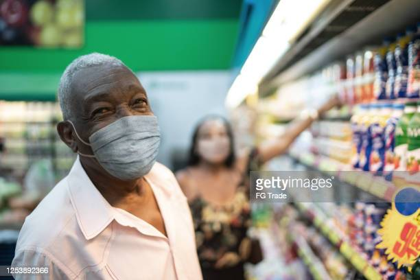 portrait of senior man with face mask shopping at supermarket - market retail space stock pictures, royalty-free photos & images