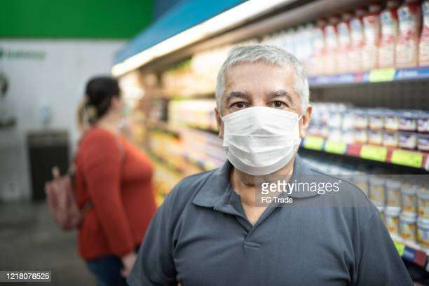 portrait of senior man with face mask shopping in supermarket - market retail space stock pictures, royalty-free photos & images