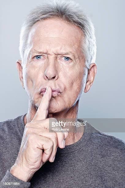 Portrait of senior man with finger on his lips, studio shot