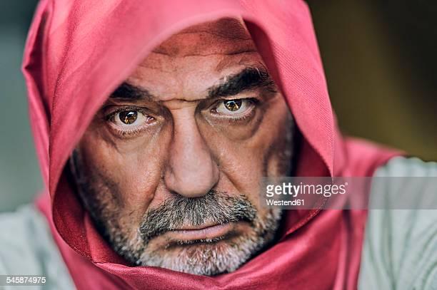 Portrait of senior man with full beard wearing red headscarf