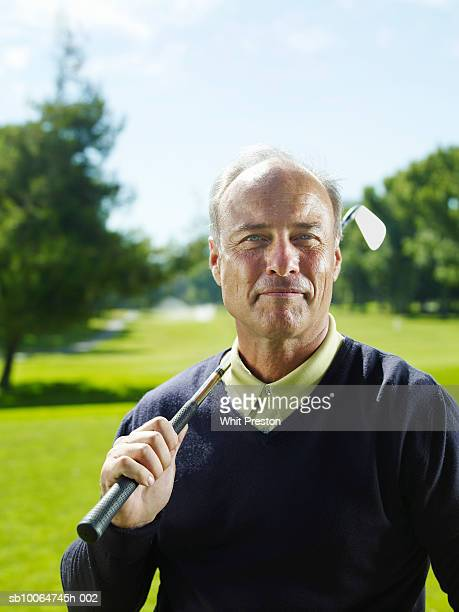 Portrait of senior man with golf club on shoulder, smiling