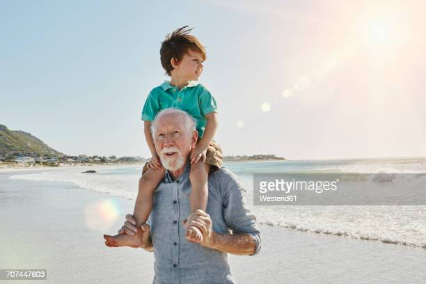 Portrait of senior man with grandson on his shoulders on the beach