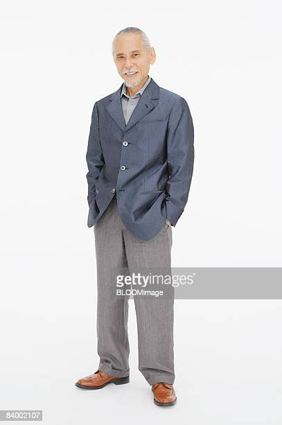 Portrait of senior man with hands in pockets, studio shot