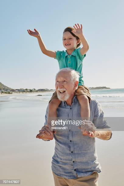 Portrait of senior man with happy grandson on his shoulders on the beach