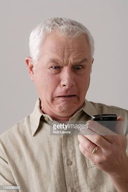 Portrait of senior man with mobile phone, studio shot