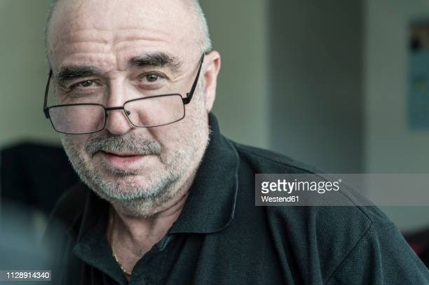 portrait of senior man with stubble wearing glasses - suspicion stock pictures, royalty-free photos & images