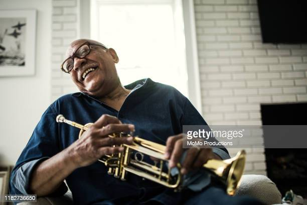 portrait of senior man with trumpet - vitalität stock-fotos und bilder