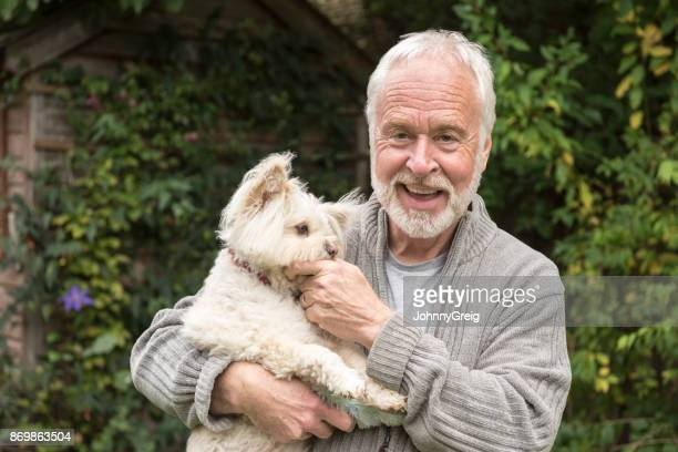 Porträt der ältere Mann mit weißem Haar und Bart Holding Hund