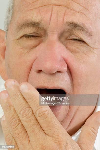 Portrait of senior man yawning