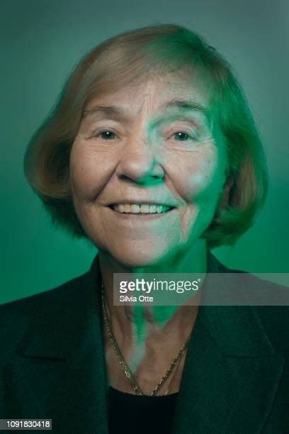 Portrait of senior, mature business woman in green light smiling