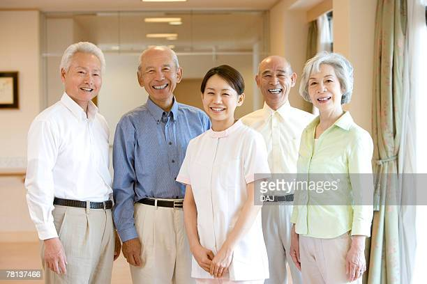 Portrait of senior men and woman with nurse smiling and looking at camera