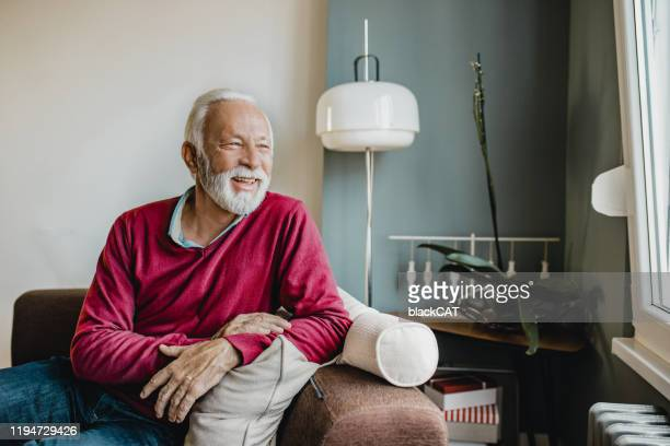 portrait of senior men at home - red shirt stock pictures, royalty-free photos & images