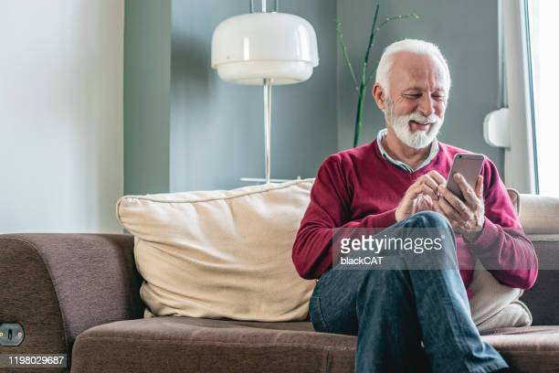 portrait of senior men at home using smart phone - red shirt stock pictures, royalty-free photos & images