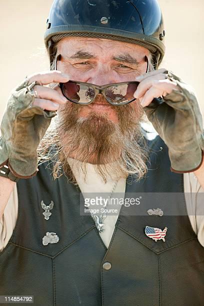 Portrait of senior motorcyclist removing sunglasses
