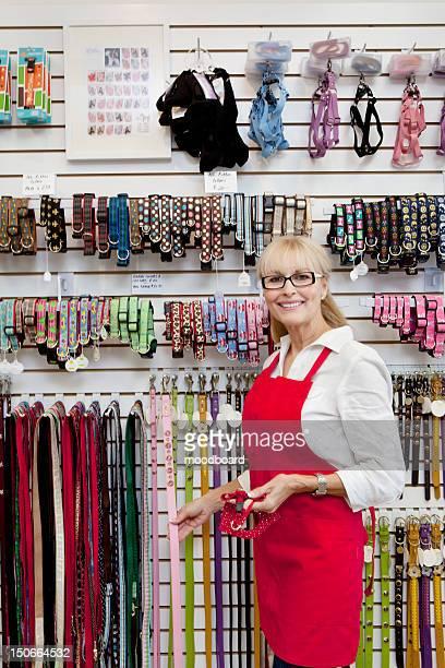 Portrait of senior owner of pet shop showing belt