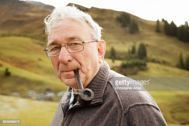 portrait of senior pipe smoker in the mountains - pipe smoking pipe stock photos and pictures