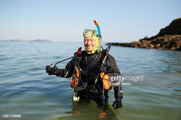 portrait of senior scuba diver standing in sea with full diving kit. - hobbies stock pictures, royalty-free photos & images