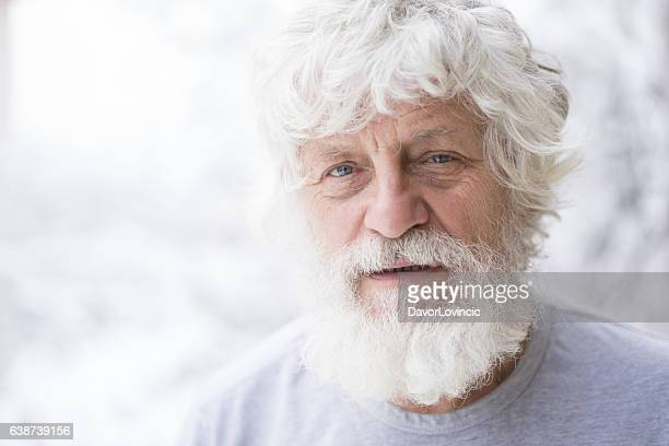 Portrait of senior with white beard and blurred snow  background
