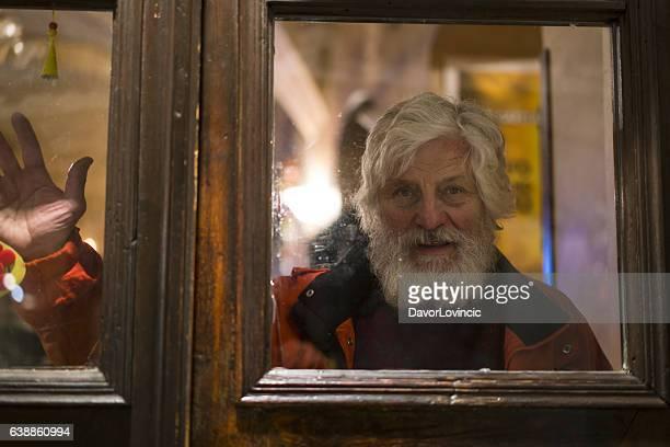 Portrait of senior with white beard behind the door window