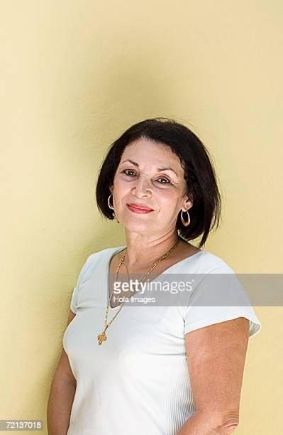 Portrait of senior woman against yellow background