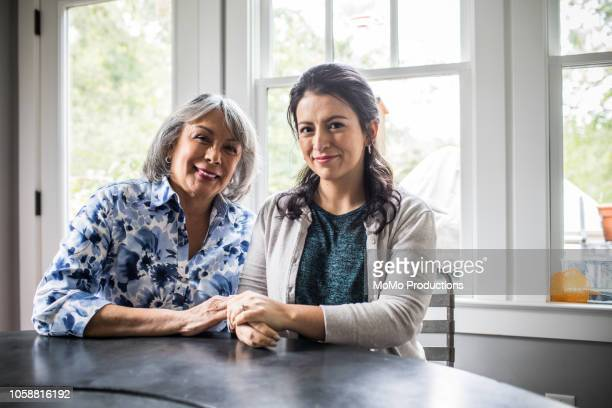 portrait of senior woman and adult daughter in kitchen - daughter stock pictures, royalty-free photos & images