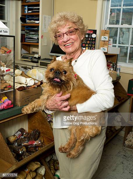 Portrait of senior woman and her dog in pet store