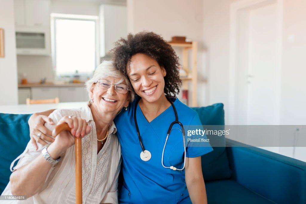 Portret van senior vrouw en haar gemengde ras vrouwelijke verzorger : Stockfoto