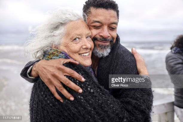 portrait of senior woman and mature man hugging by the sea - schleswig holstein stock pictures, royalty-free photos & images