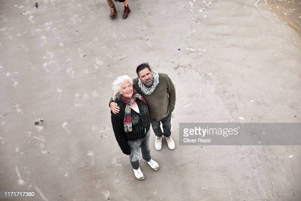 portrait of senior woman and mature man standing on the beach - nur erwachsene stock-fotos und bilder