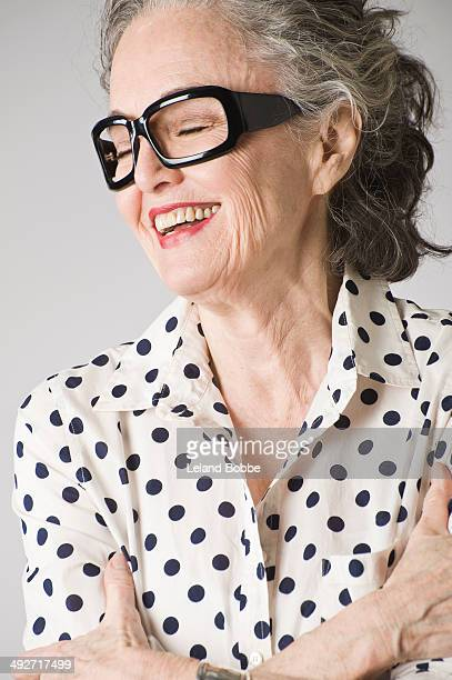 Portrait of senior woman, arms crossed, laughing