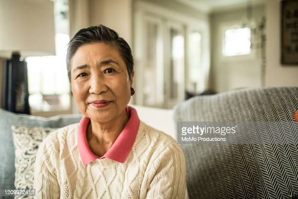portrait of senior woman at home - asiatischer und indischer abstammung stock-fotos und bilder