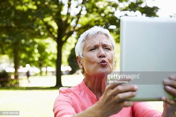 Portrait of senior woman blowing kiss and taking a self-portrait with a tablet