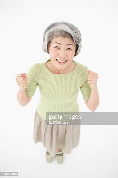 Portrait of senior woman clenching fists, high angle view, studio shot