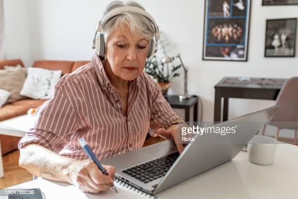 ラップトップに集中し、作業シニア女性の肖像画 - ワーキングシニア ストックフォトと画像